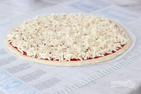 5. Из указанного количества ингредиентов получится 2 коржа. Раскатайте тесто на присыпанной мукой поверхности, смажьте соусом и распределите начинку по вкусу.