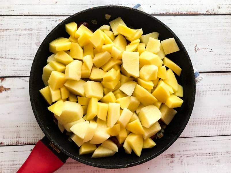 Картофель хорошо помойте, нарежьте небольшие кусочками, выложите в сковороду, перемешайте и жарьте в течение 8-10 минут.