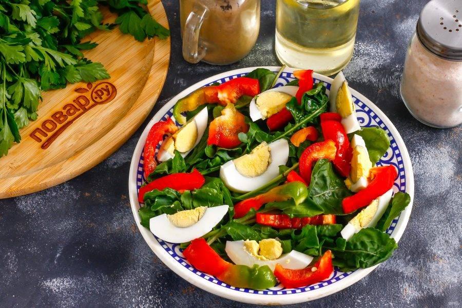 Болгарский перец любого цвета очистите от семян и промойте в воде, нарежьте ломтиками и выложите на листья рукколы.