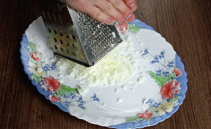 1. Яйца отвариваем, остужаем, отделяем белки от желтков. Белки трем на мелкой терке и выкладываем на дно салатницы. Смазываем майонезом.