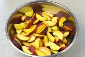 Персики моем, удаляем косточки и режем дольками. Кладем в металлическую посуду.