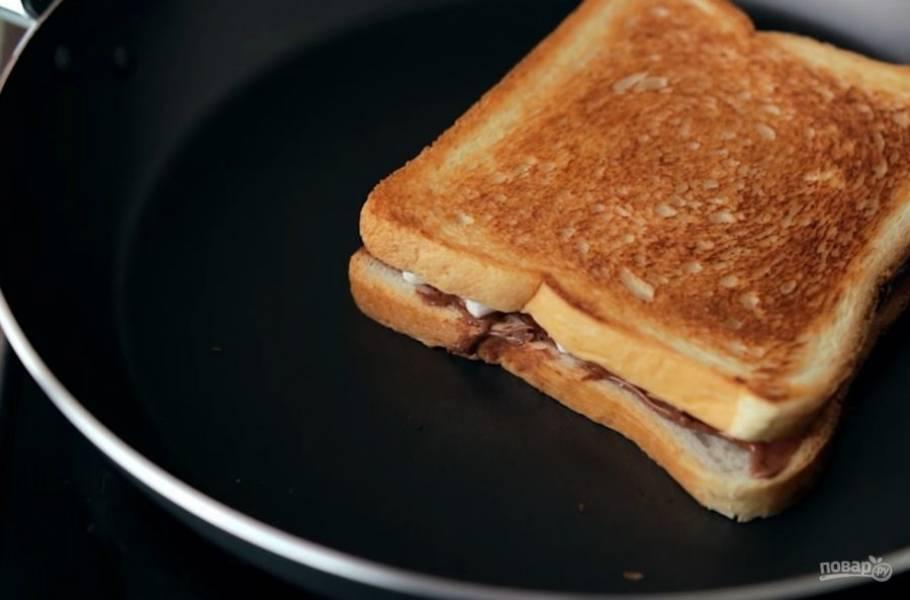 2. Далее прикройте тост вторым ломтиком хлеба и положите на разогретую сухую сковороду, чтобы хлеб немного подрумянился. Когда одна сторона хлеба станет достаточно хрустящей, переверните его и подсушите с второй стороны.