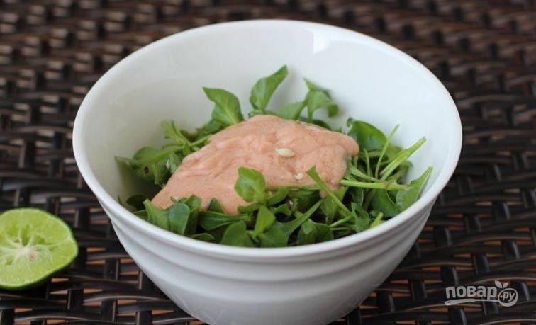 Вымойте под проточной водой пучок зелени. Для этого салата идеально подойдет кресс-салат, но вы можете использовать любой другой сорт. Порвите его руками и положите в миску. Залейте заправкой.