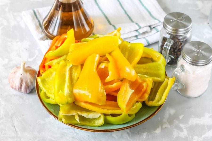 Перец промойте в воде, срежьте крышечки с хвостиками, удалите семена и разрежьте очищенные плоды на части. Промойте в воде.