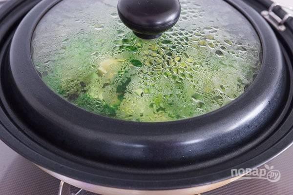 4.Верните сковороду на огонь и влейте 2 столовые ложки воды, выложите брокколи и накройте крышкой, готовьте 2 минуты.