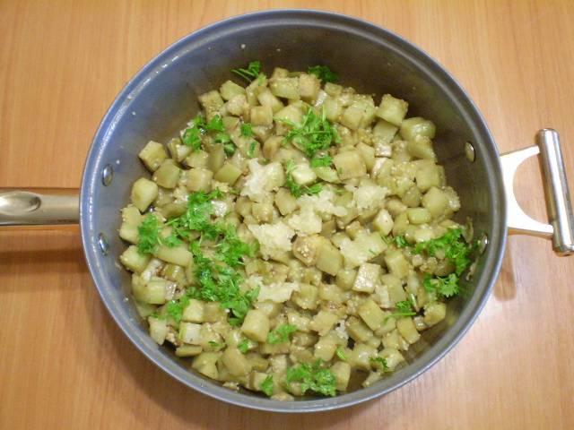 6. К практически готовым баклажанам нужно добавить чеснок, пропущенный через пресс. Также приветствуется любая зелень.