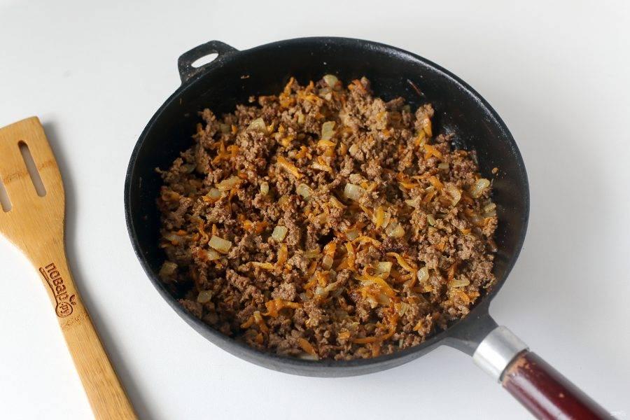 Обжарьте фарш с добавлением лука, моркови, соли и специй до полуготовности, разбивая комочки лопаткой.