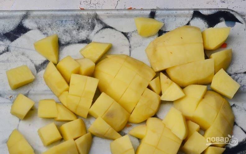 Картофель вымойте и очистите от кожуры. Затем нарежьте его кубиками небольшого размера. На плиту поставьте кастрюлю и влейте в нее куриный бульон. Доведите его до кипения.