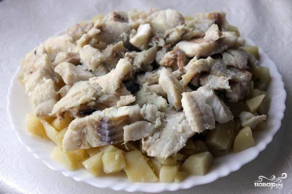 Извлекаем из бульона картофель и выкладываем его на тарелку. Сверху кладем рыбу.