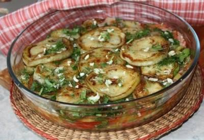 6. Теперь самый важный этап - сервировка блюда. Первым слоем кладем баклажан, сверху притрушиваем чесноком, затем помидоры с луком и в завершении - зелень.