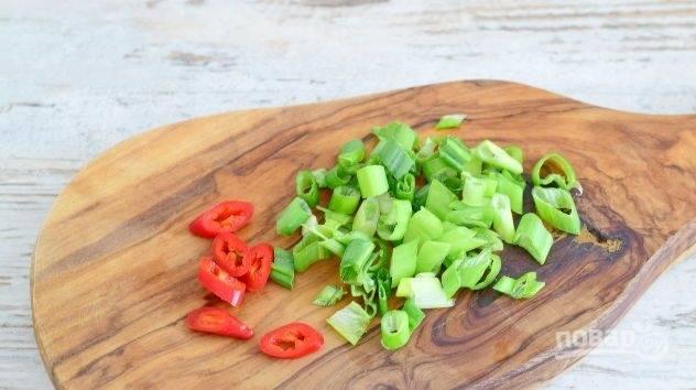 В это время нарежьте небольшими колечками перец чили и зелёный лук.