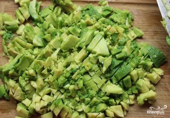 Спелое авокадо разрежьте на две части, достаньте косточку. Достаньте мякоть ложкой, а шкурку оставьте. Она будет служить своеобразной тарелкой для салата. Нарежьте фрукт ножом на мелкие кусочки.
