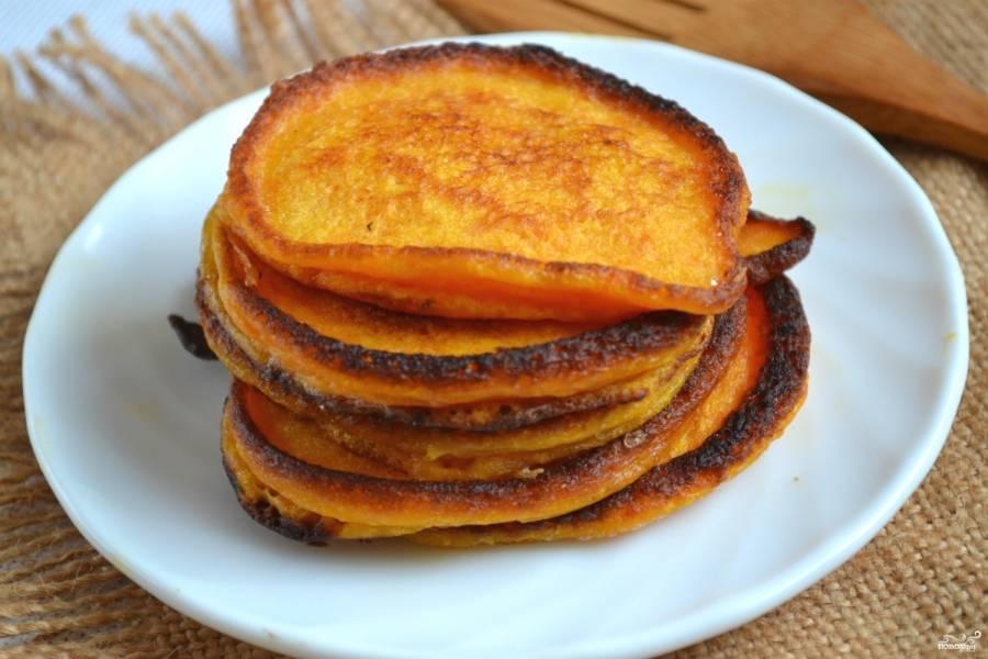 Готовые оладки выложите на тарелку, слегка остудите и подавайте к столу. К тыквенным оладьям хорошо подойдет ароматное яблочное варенье или мед.
