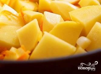 Добавьте к луку и чесноку нарезанную или натертую морковь, тушите еще пять-десять минут. Картошку очистите от кожуры, вымойте и нарежьте крупными кусками. Добавьте в чугунок картофель, посыпьте его специями, перемешайте.