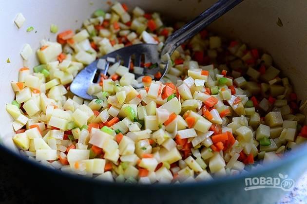 Картошку почистите, порежьте мелким кубиком и отправьте на сковороду к овощам.