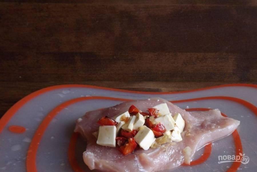 Выложите в средину куриного филе обжаренный перец с чесноком и нарезанным сыром.