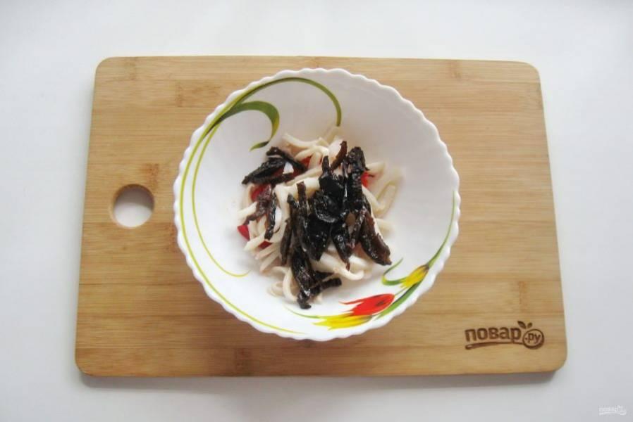 Чернослив помойте и залейте кипятком, дайте постоять 10 минут. Затем нарежьте соломкой и добавьте в салат.