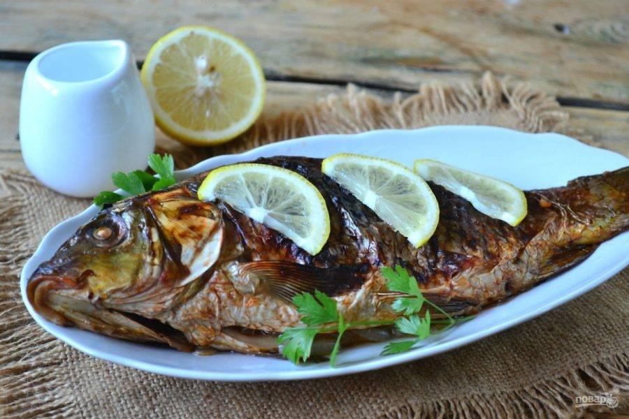 Через 20 минут после начала запекания фольгу разверните, чтобы на поверхности рыбки образовалась поджаристая корочка. Подавайте запеченного сазана, выложив на овальную тарелку и украсив зеленью и ломтиками лимона. Кушайте с удовольствием!