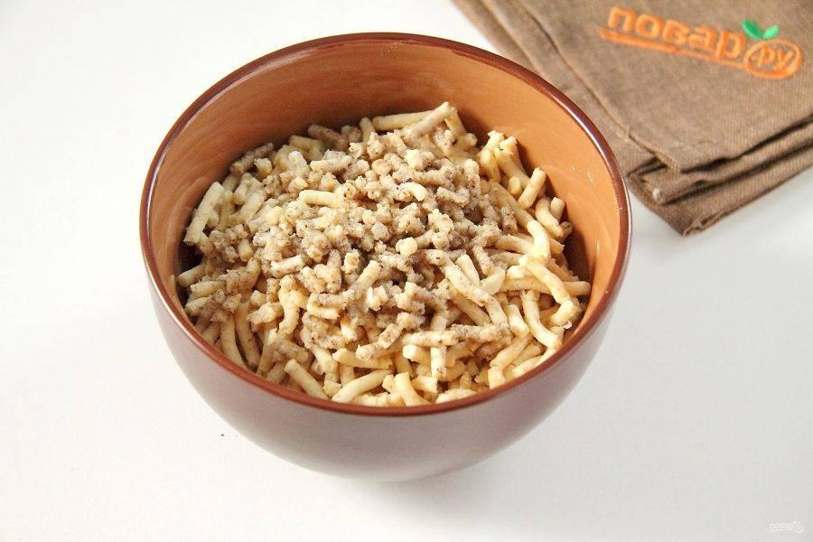 Измельчите нут в мясорубке или при помощи блендера. Грецкие орехи измельчите таким же способом и добавьте к нуту.