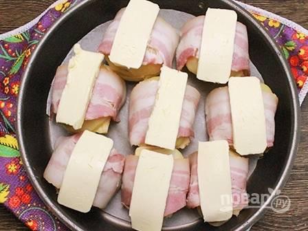 Дно формы застилаем пергаментом и выкладываем картофель. На верхушку каждой обернутой картофелины выкладываем тонкую пластинку сливочного масла.