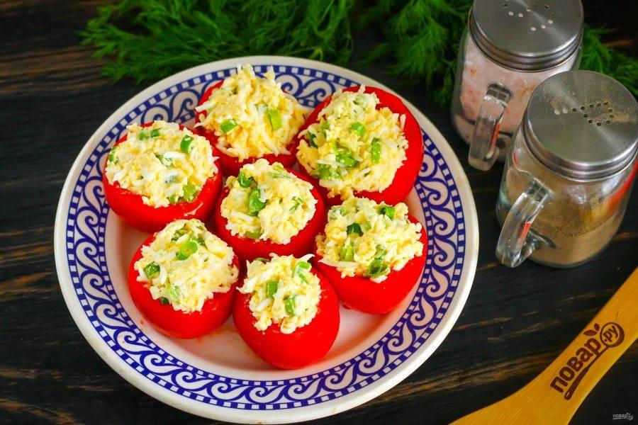 Начините очищенные помидоры яичным салатом до верха с помощью чайной ложки. Если помидоры крупные, то вам придется увеличить количество начинки, отварив и натерев еще несколько куриных яиц.