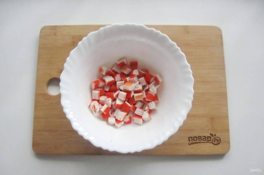 Крабовые палочки нарежьте кубиками и выложите в салатник.