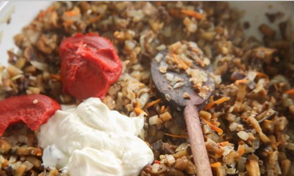 1. Для начала измельчим мясо, грибы, баклажан и лук с морковкой как можно мельче. Обжарим эту смесь со специями. Когда лук станет прозрачным, а мясо подрумянится, добавим томатную пасту и сметану. Перемешаем, на маленьком огне тушим до готовности.