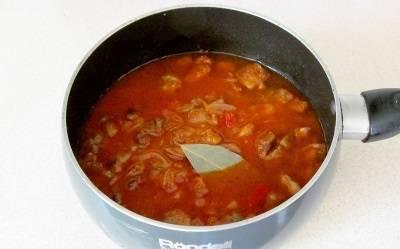Вливаем кипяченую воду, чтоб покрылось все мясо. кладем лавровый лист, варим 25-30 минут под крышкой. Подлива должна загустеть, а мясо стать мягким.