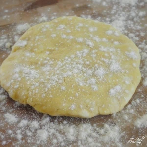 Тесто достаем из холодильника, выкладываем на присыпанную мукой поверхность и раскатываем в круг диаметром около 30 см.