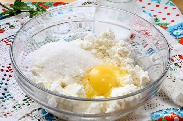 Творог хорошо разминаем, чтобы не было комочков. Добавляем к нему яйцо и полторы ложки сахара. Перемешиваем все до однородной массы.