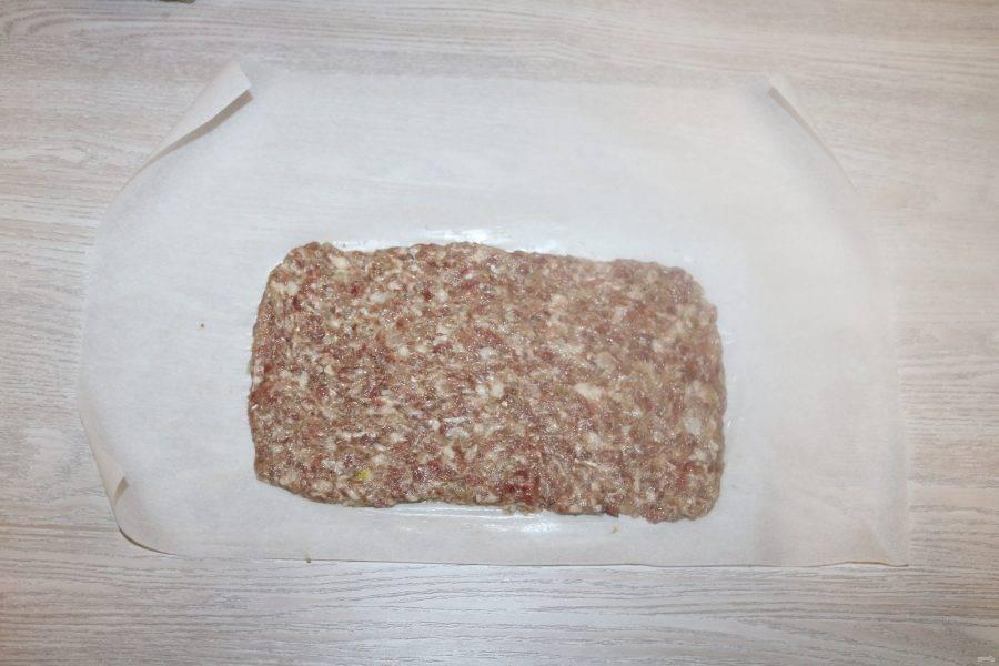 На лист пекарской бумаги выложите фарш равномерно тонким слоем в виде прямоугольника.