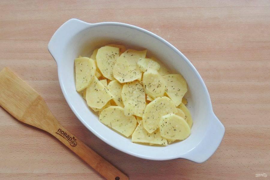Картофель отварите до полуготовности. Охладите и нарежьте пластинками. Выложите в форму для запекания, посолите и поперчите.