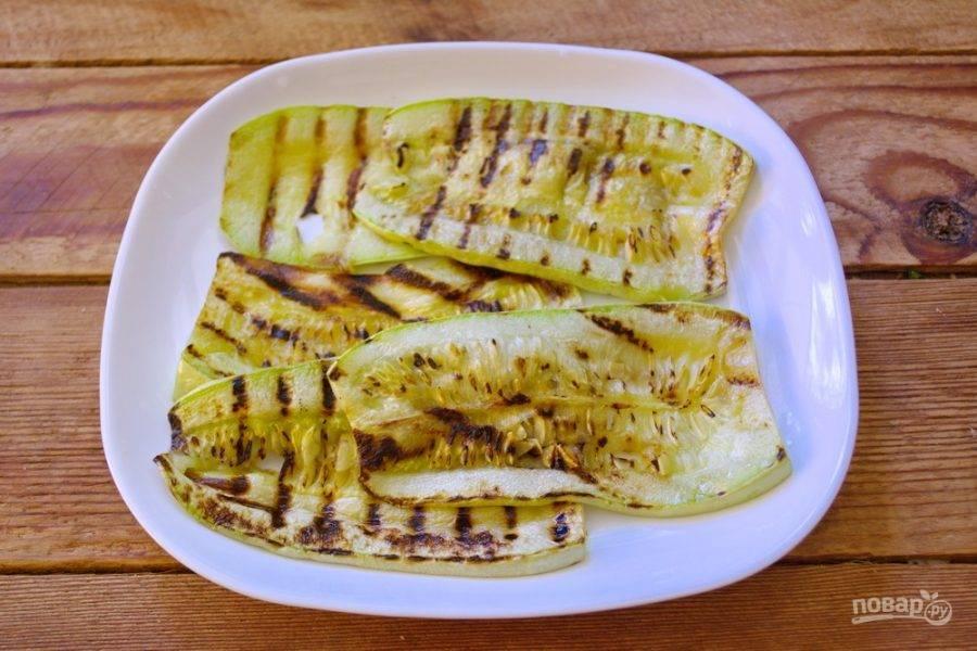 Снятые с гриля кабачки уложите аккуратно на тарелку. Дайте немного остыть. После остывания кабачки станут мягче, их будет легче скручивать.
