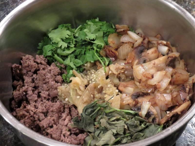 Теперь мы соединяем в миске обжаренный фарш, грибы с луком и мякоть баклажана, добавляем панировочные сухари, яйцо, петрушку, укроп, пармезан.