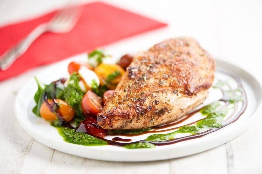 6. На тарелку для подачи выложите помидоры с сыром. Рядом разложите шпинат. На него положите курицу. Полейте блюдо уксусом и песто. Приятного аппетита!