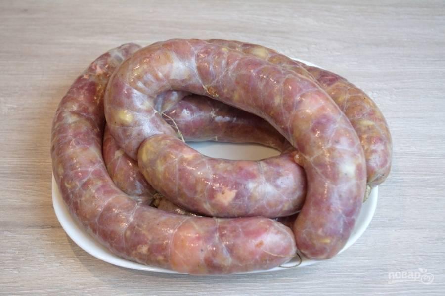 Включите мясорубку, партиями кладите в неё мясо. Вал, вращаясь, направит мясо прямо в кишку. Придерживая саму кишку, наполняйте колбасу. Через каждые 30-40 см. останавливайте процесс. Перевяжите кишку, разделив всю колбасу на сосиски. Если всю колбасу сделать одним целым, то при запекании или последующей обработке она треснет и фарш выйдет наружу. Так наполните всю кишку.