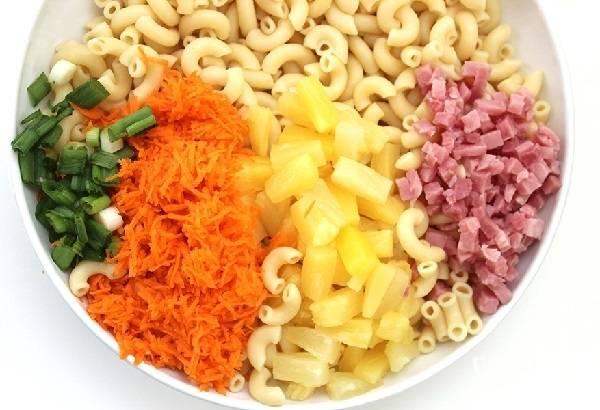 5. В глубоком салатнике соедините макароны, нарезанные кубиками ветчину и ананасы, тертую морковь, измельченный зеленый лук.