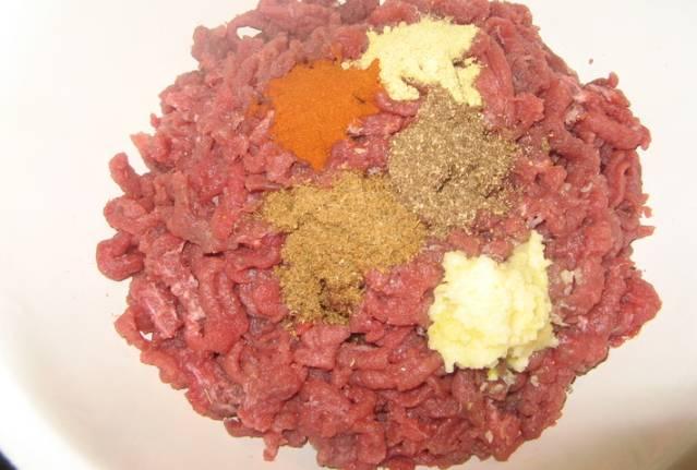 Добавляем в мясо пряности, перемешиваем.
