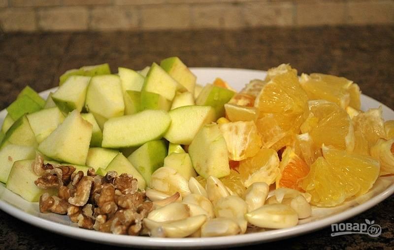 Подготовьте начинку. Нарежьте кубиками яблоки и апельсины. Орехи порубите, а чеснок очистите.