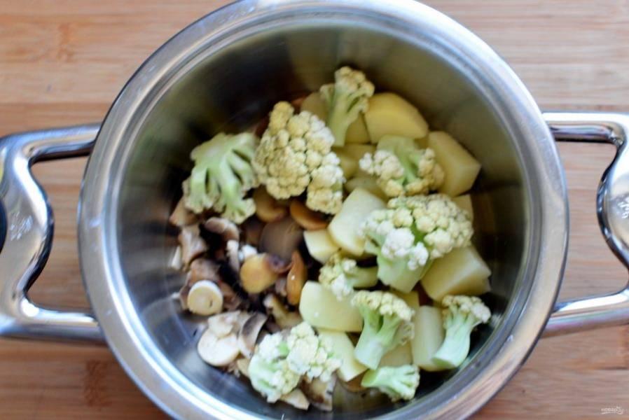 Остальные грибы выложите в кастрюлю, добавьте нарезанный картофель и разобранную на соцветия капусту.