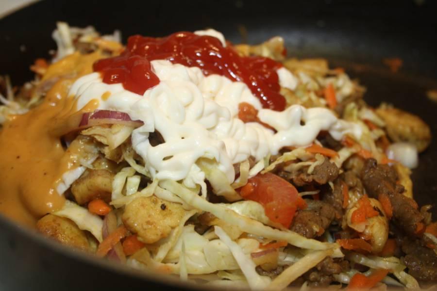 2. Далее уменьшим огонь, добавим мелко шинкованную капусту, лук полукольцами, измельченную морковь и кусочки помидоров. Кетчуп, майонез и горчицу тоже вливаем сейчас. Перемешаем и тушим до готовности. Специи - по вкусу.