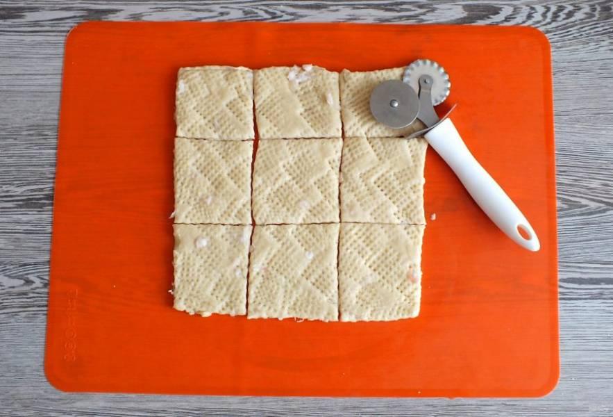 С помощью резака или ножа, обрежьте неровные края, чтобы образовался квадрат. Квадрат разделите на три полосы, которые разрежьте на квадратики. Из обрезков раскатайте повторно пласт и нарежьте таким же образом печенье.
