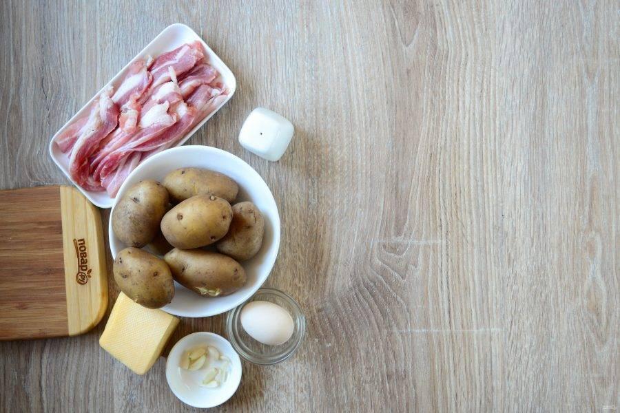 Подготовьте все необходимые ингредиенты. Картофель отварите в мундире до готовности, затем воду слейте, а самому картофелю дайте слегка остыть.