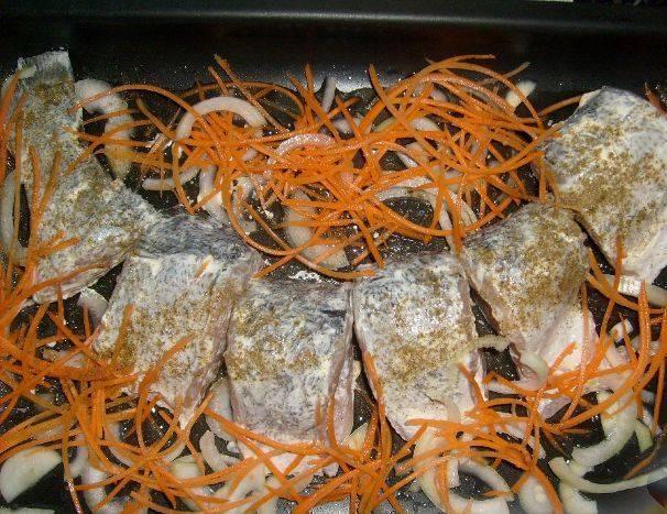 3. Выкладываем рыбу на смазанный маслом противень  и рядом выкладываем лук и морковь.