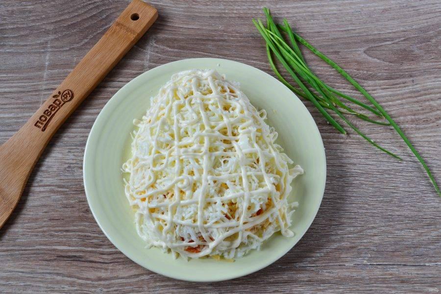 5. Яйца разделите на белки и желтки. Белки натрите на мелкой терке и выложите на сыр. Сверху хорошенько смажьте майонезом, я покрыла сеточкой из майонеза. Это нужно для того, чтобы верхний декоративный слой хорошо пристал и салат держал форму. На этом де этапе необходимо придать форму салату – овал, нужно, чтобы он получился ровненьким и красивым.