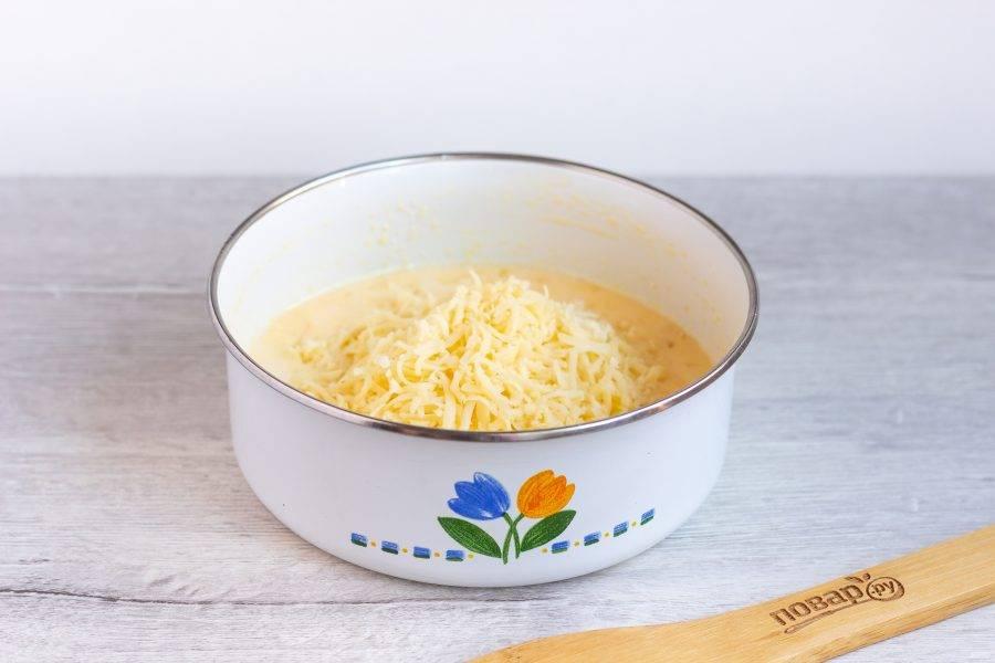 Сыр натрите на мелкой терке, по истечении времени добавьте в яичную массу и перемешайте.