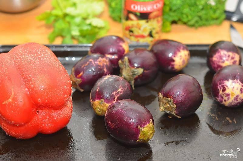 Моем баклажаны и красный перец, даем обсохнуть. Делаем в них небольшие надрезы, смазываем оливковым маслом и отправляем в духовку на 25-30 минут. Запекаем до готовности.