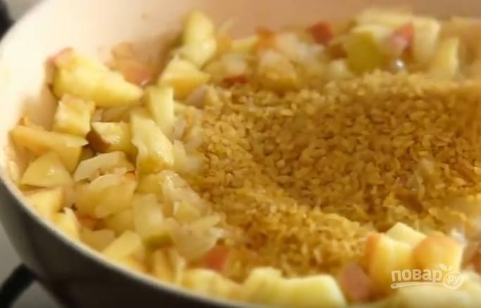 3. Поджарьте в оливковом масле лук, затем добавьте яблоки и жарьте еще 3 минуты. Добавьте булгур, посолите, перемешайте и тушите 10 минут на медленном огне. Накройте крышкой и оставьте, чтобы крупа набухла.