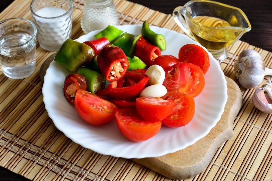 Почистите сладкий перец от семян. У острого можно оставить семена, чтобы приправа получилась более жгучей. Чеснок почистите. Овощи нарежьте произвольными кусочками: перец - два вида, помидоры и чеснок.