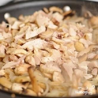 7. Добавьте к луку нарезанные грибы и курицу. Поперчите и перемешайте.